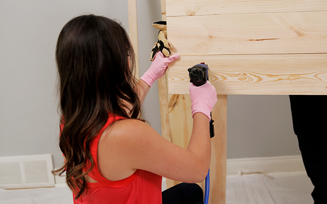 Woman nails pieces of the headboard together.
