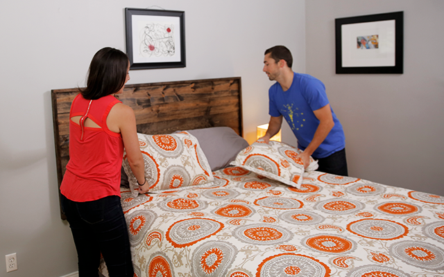 Couple tosses pillows on the bed with finished headboard.